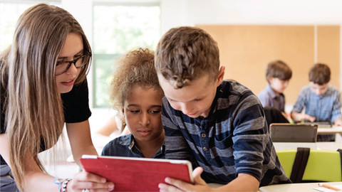 Three students looking at tablet in classroom