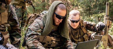 Men in camouflage gear working on a laptop in the field